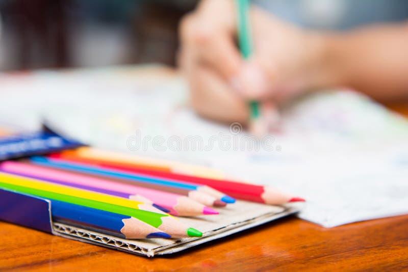 La muchacha está pintando en los libros de colorear imagen de archivo