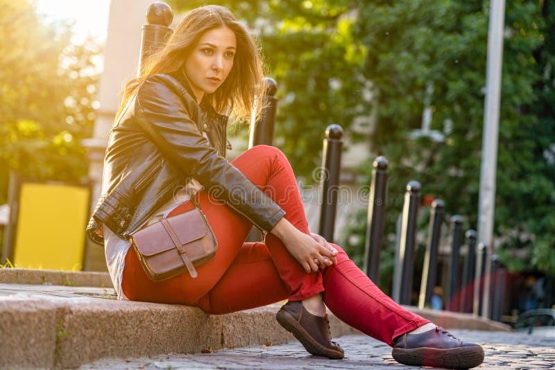 La muchacha está planteando la sentada atractiva en el encintado en pantalones rojos, chaqueta negra al aire libre Fotografía de  imagen de archivo libre de regalías
