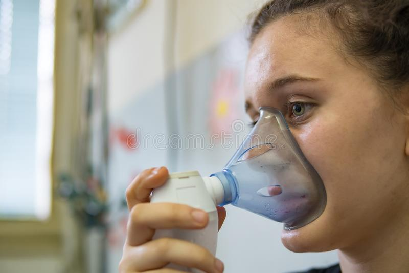 La muchacha está rociando los broncodilatadores para tratar a corredores respiratorios de los síntomas en la sala de urgencias de foto de archivo
