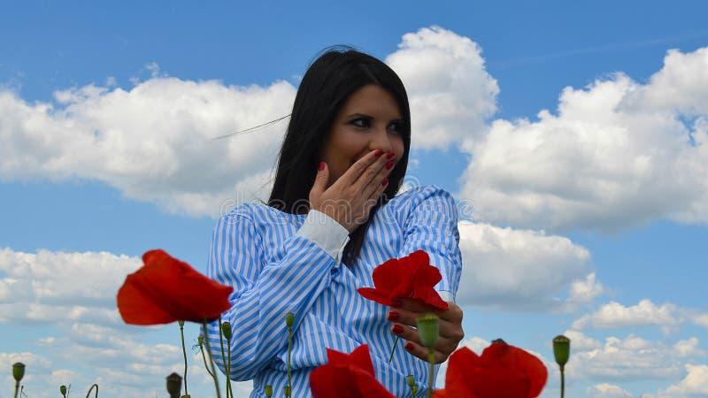 La muchacha está sonriendo en el campo de la amapola de flores imagen de archivo libre de regalías