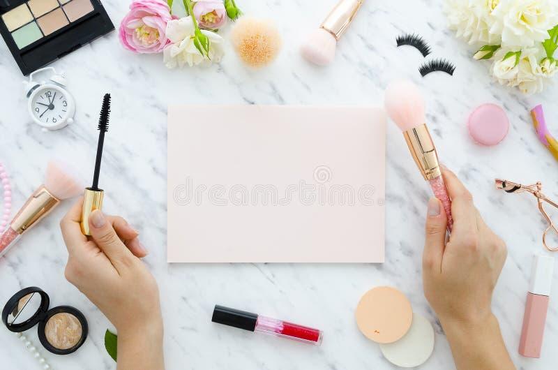 La muchacha está sosteniendo el rimel en manos, espacio de la copia para el cuaderno manuscrito del rosa de la cita, lápiz labial imágenes de archivo libres de regalías