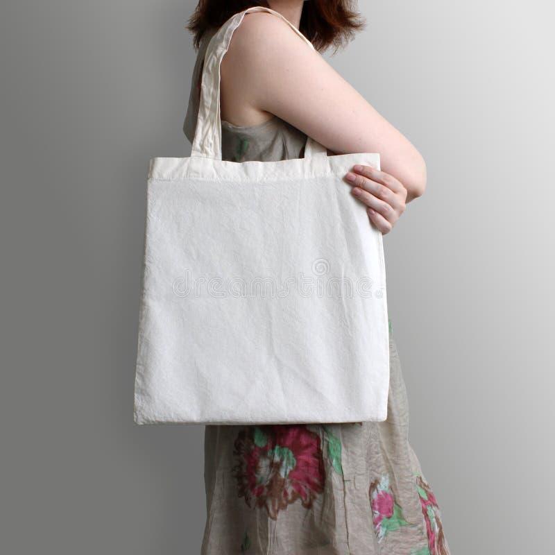 La muchacha está sosteniendo la bolsa de asas en blanco del eco del algodón, maqueta del diseño fotos de archivo