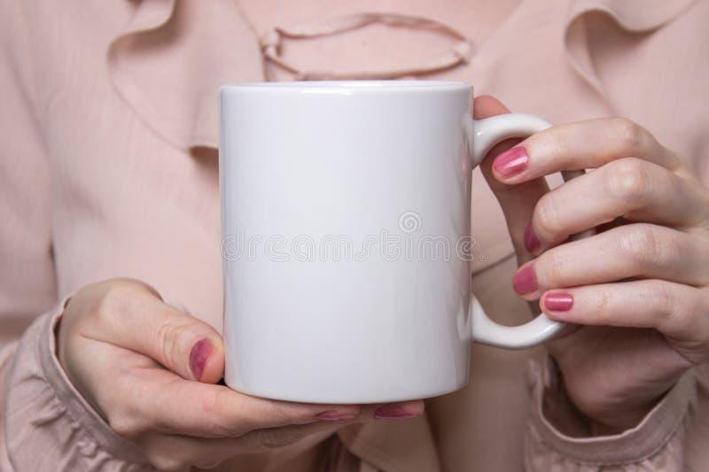 La muchacha está sosteniendo la taza blanca en manos Taza blanca para la mujer, regalo Maqueta para los diseños imágenes de archivo libres de regalías