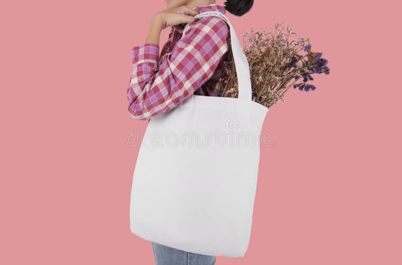 La muchacha está sosteniendo la tela de la lona del bolso con la flor para el espacio en blanco de la maqueta imágenes de archivo libres de regalías