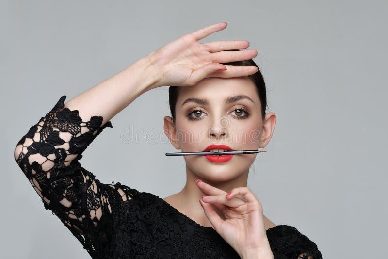 La muchacha está sosteniendo un cepillo para los cosméticos en sus dientes en a levemente imagen de archivo
