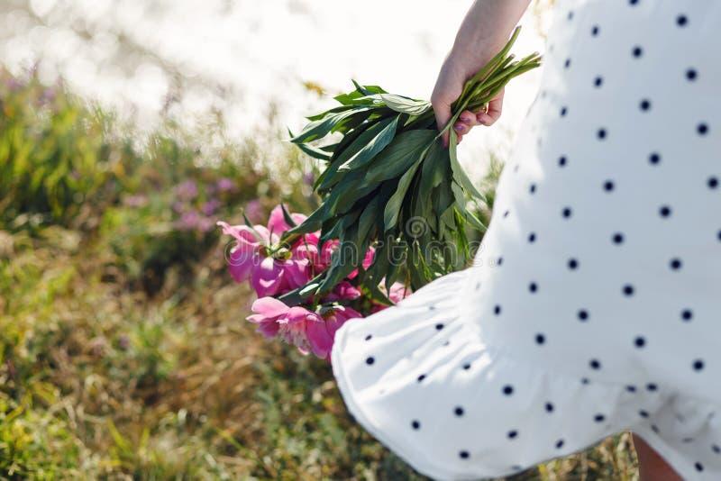 La muchacha está sosteniendo un ramo de peonías rosadas florecientes hermosas Sus alborotos blancos del vestido en el viento imagen de archivo libre de regalías