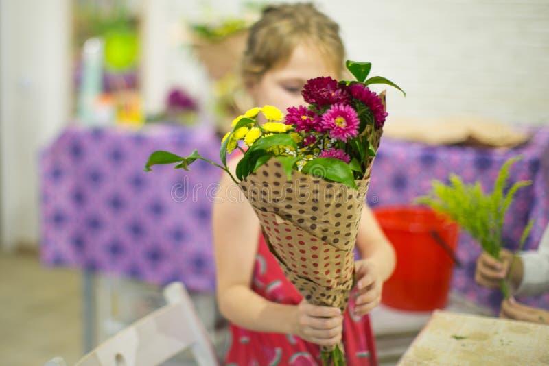 La muchacha está sosteniendo un ramo listo de flores fotos de archivo