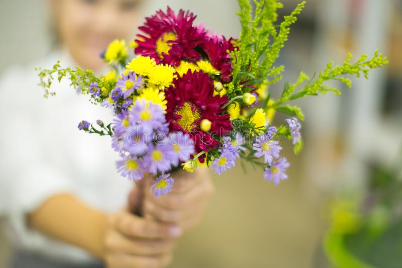 La muchacha está sosteniendo un ramo listo de flores fotografía de archivo