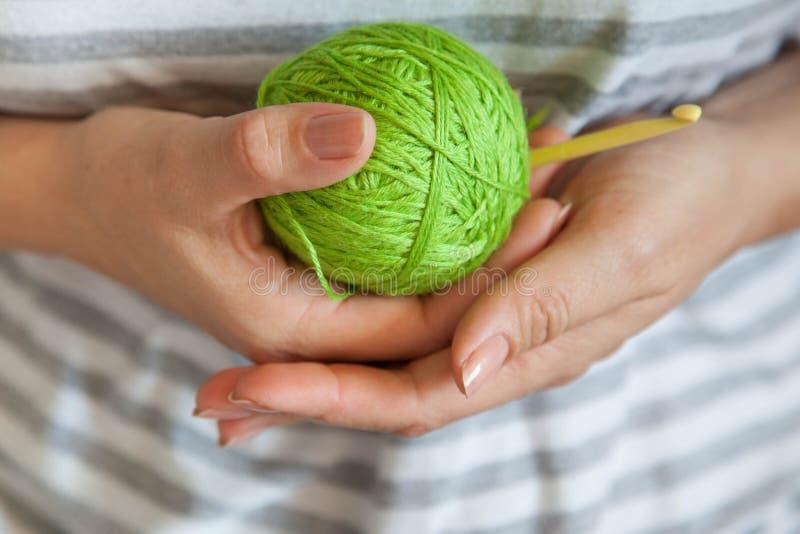 La muchacha está sosteniendo una bola del hilado de lana verde claro imagenes de archivo