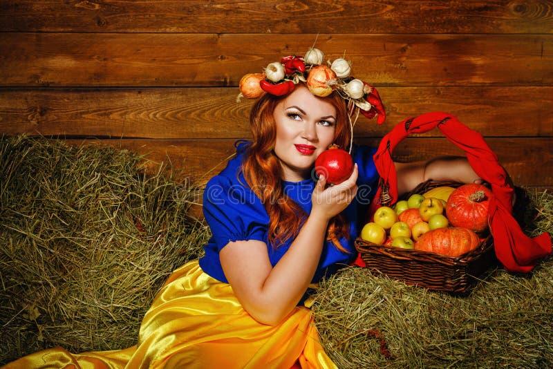 La muchacha está sosteniendo una fruta de la granada fotos de archivo libres de regalías