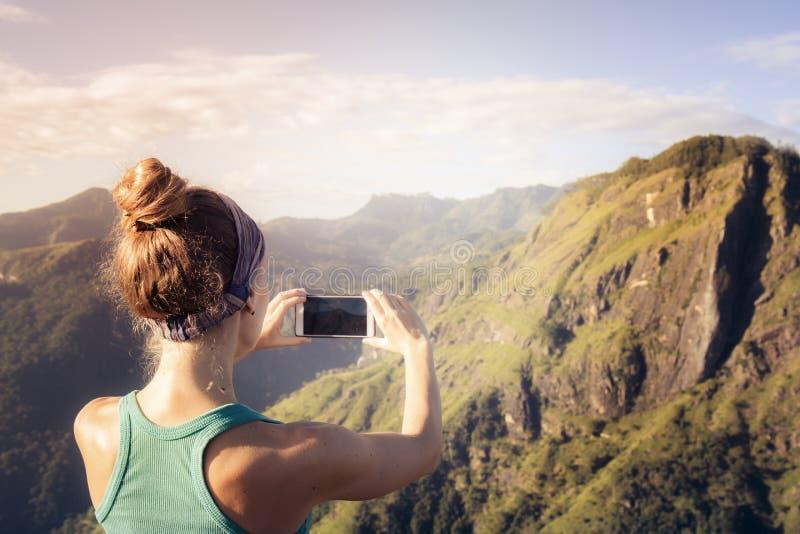 La muchacha está tomando imágenes en los rayos del amanecer foto de archivo libre de regalías