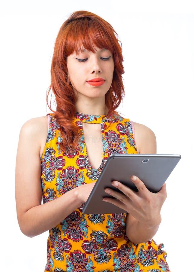 La muchacha está utilizando la tableta Mujer joven del pelirrojo con el vestido del verano imágenes de archivo libres de regalías