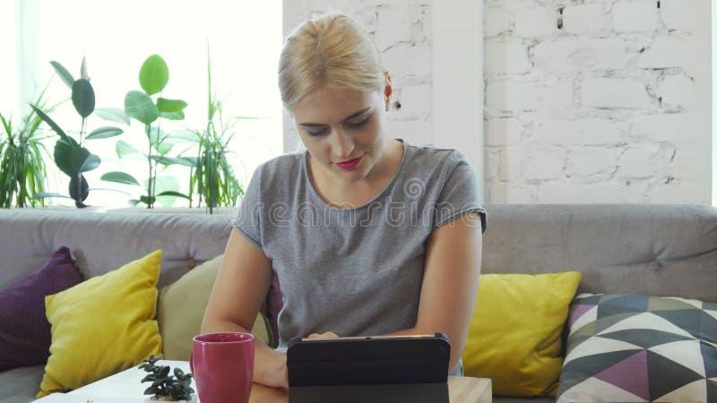 La muchacha está utilizando su tableta fotografía de archivo libre de regalías