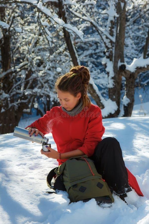 La muchacha está viajando a través de un bosque del invierno vierte el café del termo fotografía de archivo