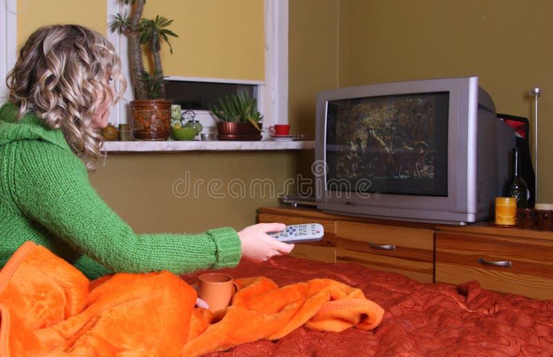 La muchacha está viendo la TV fotografía de archivo