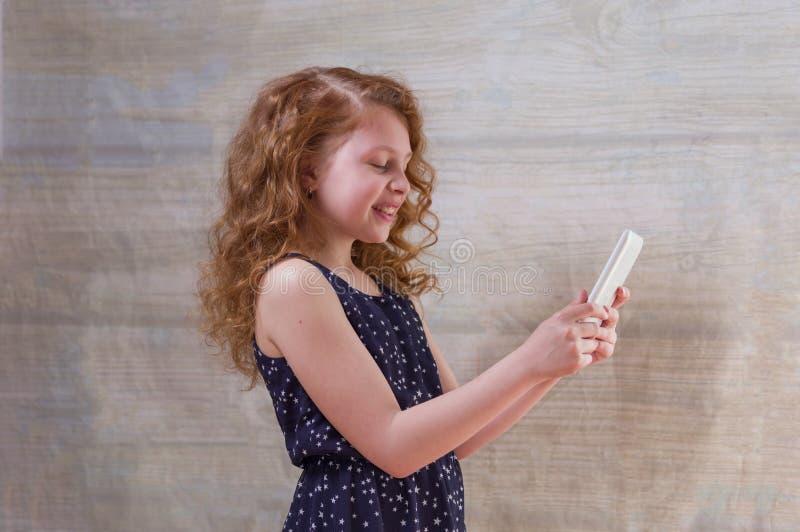 La muchacha est? sosteniendo una tableta La muchacha con sus ojos se cerr? Esperar una sorpresa fotografía de archivo libre de regalías