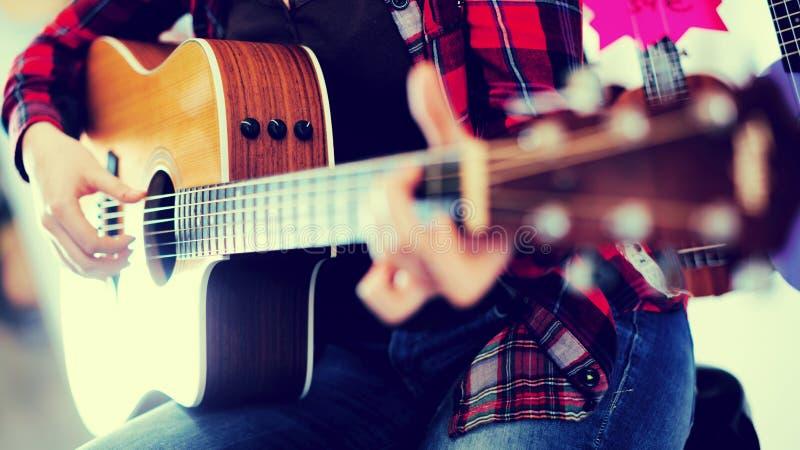 La muchacha est? tocando la guitarra ac?stica Foco en el cuerpo de la guitarra fotografía de archivo libre de regalías