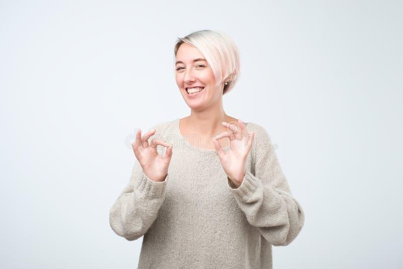 La muchacha europea divertida positiva con el pelo corto teñido en ropa casual muestra la muestra aceptable, demuestra que todo e fotos de archivo