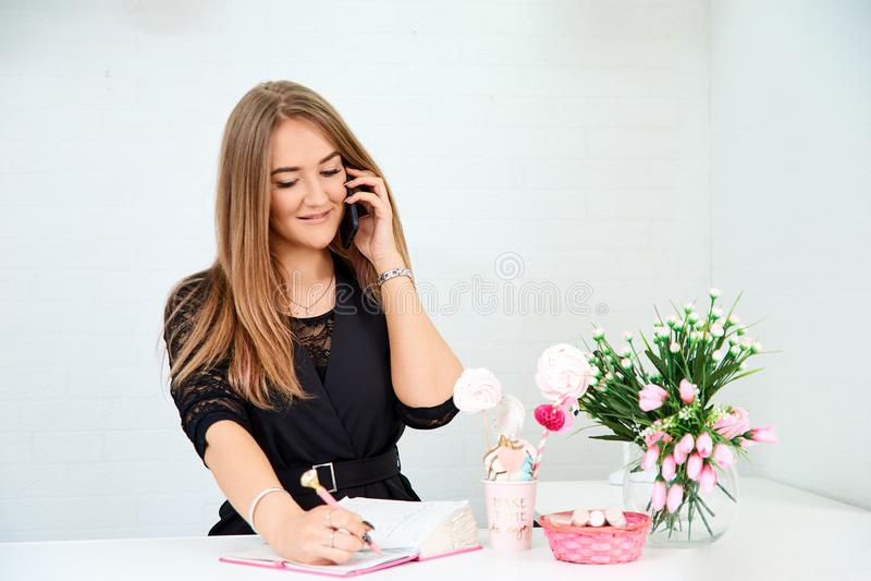 la muchacha europea hermosa toma una llamada en el teléfono y escribe en un cuaderno en un fondo blanco Cerca están las flores y foto de archivo