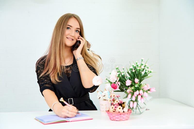la muchacha europea hermosa toma una llamada en el teléfono y escribe en un cuaderno en un fondo blanco Cerca están las flores y imágenes de archivo libres de regalías