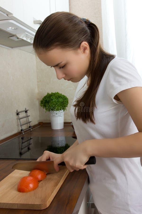 La muchacha europea joven con el pelo largo prepara la comida fotos de archivo