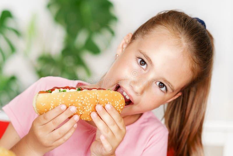La muchacha europea linda joven en camiseta está comiendo la comida malsana como el perrito caliente y microprocesadores imagenes de archivo