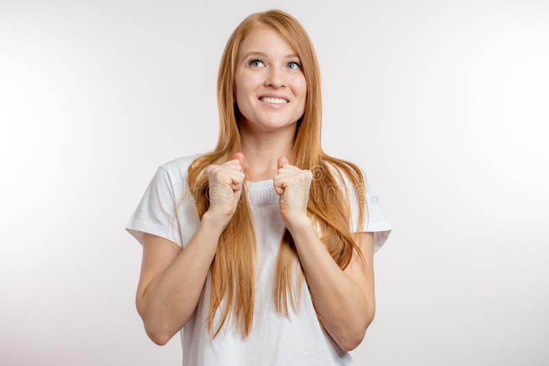 La muchacha extática hermosa está aumentando los puños apretados imagen de archivo libre de regalías