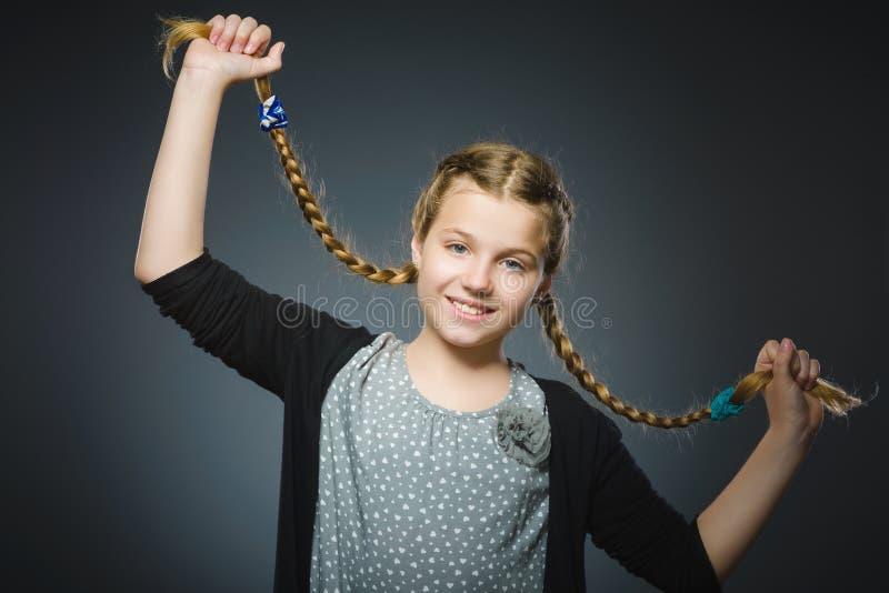 La muchacha feliz acertada del retrato del primer aisló el fondo gris fotos de archivo