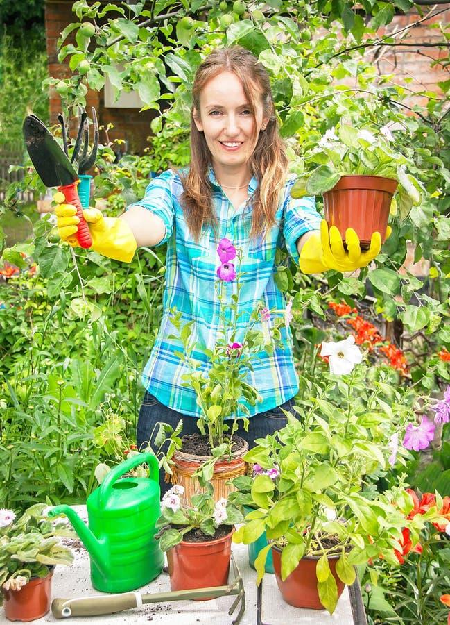 La muchacha feliz activa del jardinero está sosteniendo el pote de la flor y de Gard imágenes de archivo libres de regalías