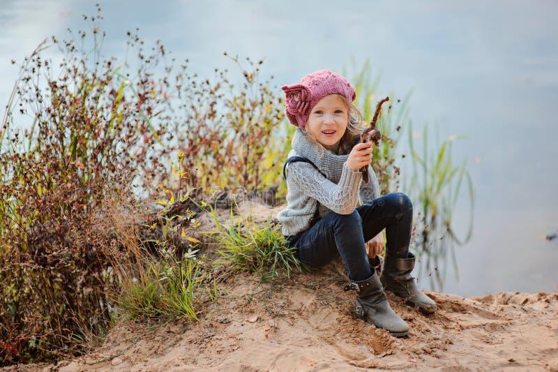 La muchacha feliz adorable del niño juega con el palillo en lado del río en día de verano imagenes de archivo