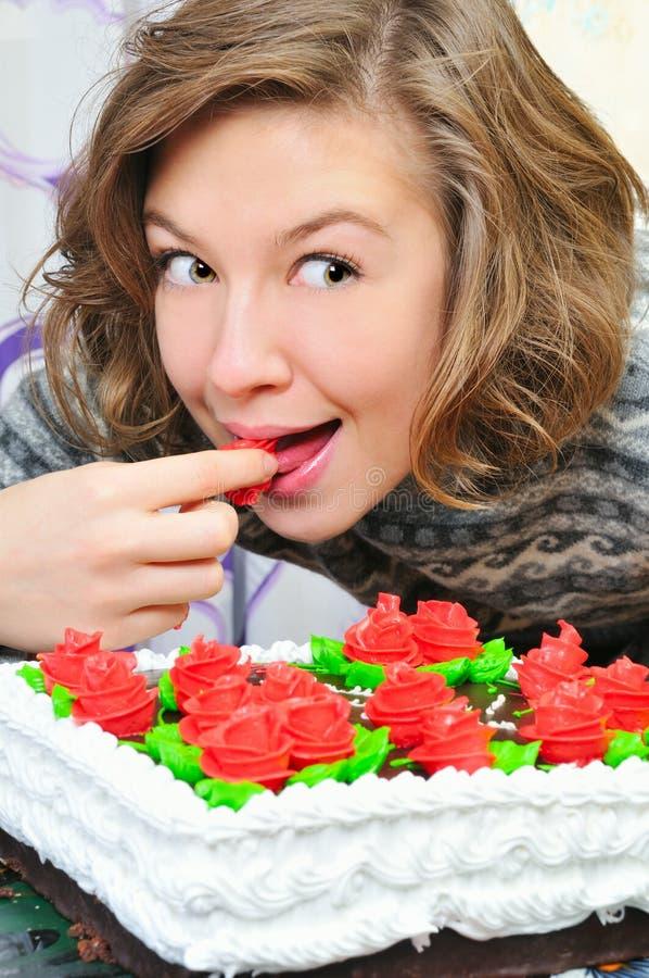La muchacha feliz come la torta fotos de archivo libres de regalías