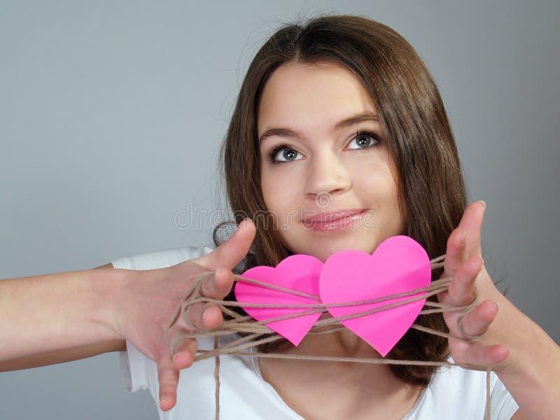 La muchacha feliz con dos corazones rosados fotos de archivo