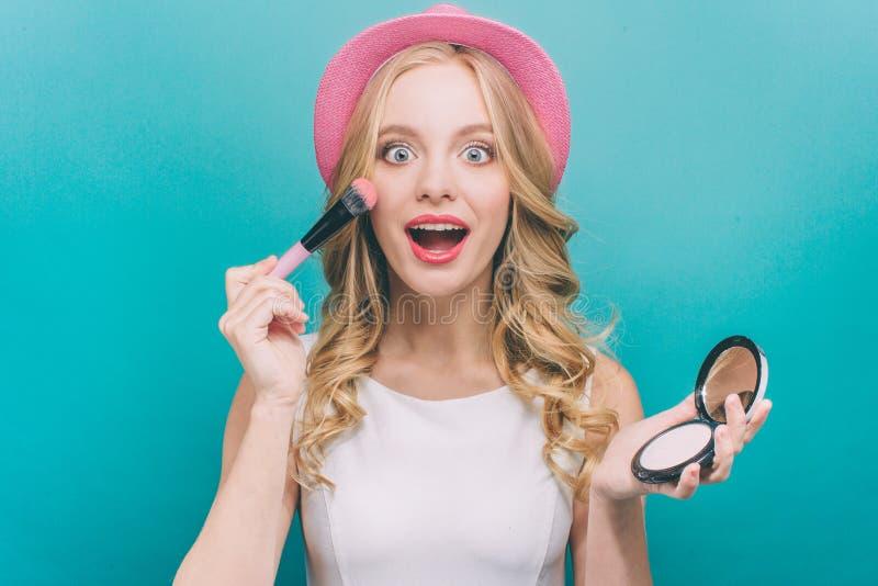 La muchacha feliz con el pelo rubio lleva calor rosado Ella tiene algún cosmatics en sus manos La muchacha está poniendo alguno s foto de archivo libre de regalías