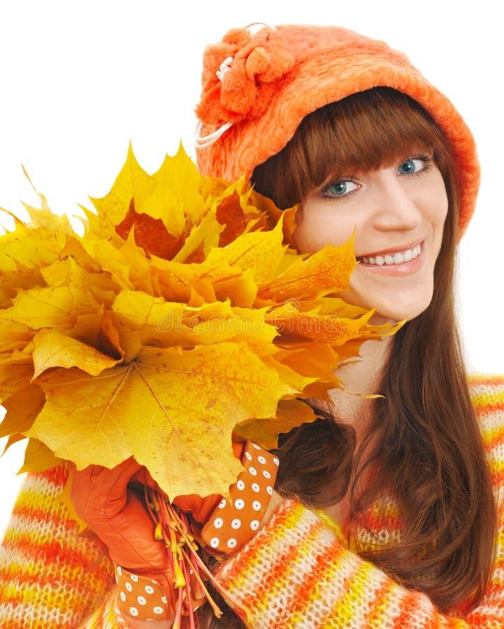 La muchacha feliz con las hojas amarillas mira en cámara fotos de archivo