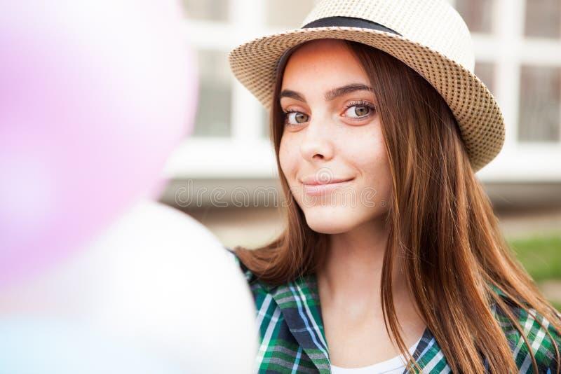 La muchacha feliz con los globos sonríe en la cámara foto de archivo