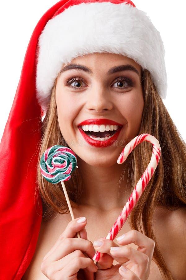 La muchacha feliz con los labios rojos y en sombrero de la Navidad está celebrando la piruleta y la sonrisa de la Navidad dos Ais fotos de archivo