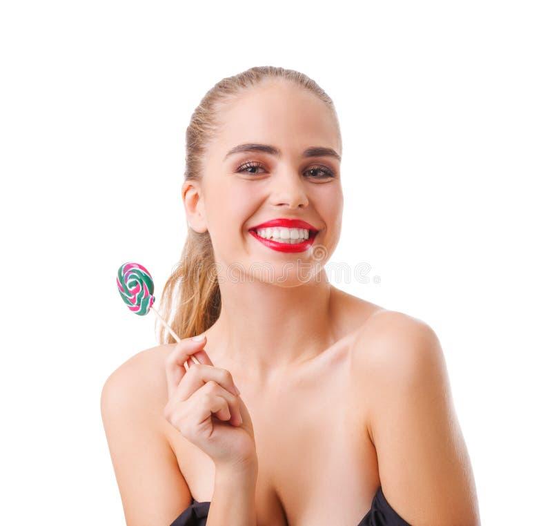 La muchacha feliz con una sonrisa sostiene una piruleta en un fondo aislado blanco imagenes de archivo