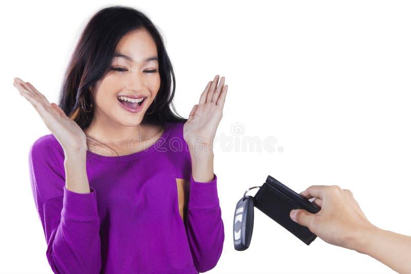 La muchacha feliz consigue una nueva llave del coche imagen de archivo libre de regalías