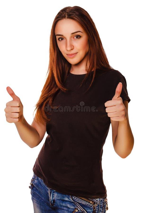 La muchacha feliz de la mujer joven muestra los pulgares del signo positivo fotografía de archivo