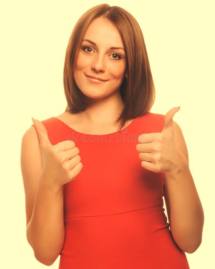 La muchacha feliz de la mujer joven muestra los pulgares del signo positivo sí, el Dr. anaranjado fotos de archivo