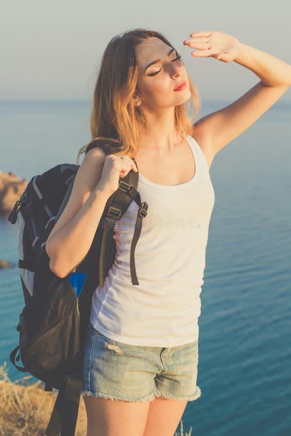 La muchacha feliz del backpacker se está colocando en roca encima fotografía de archivo