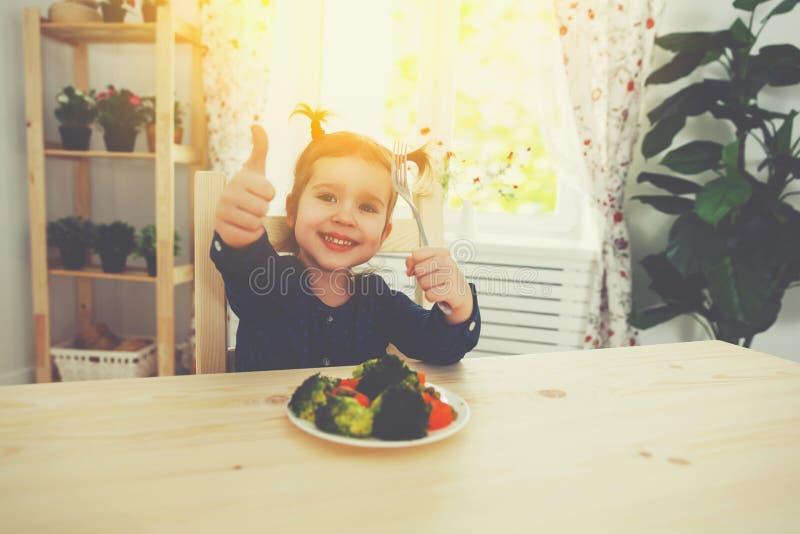 La muchacha feliz del niño come verduras y el mostrar los pulgares para arriba imagen de archivo