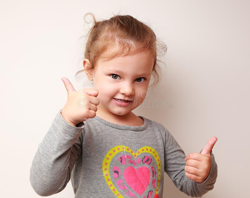 La muchacha feliz del niño que muestra los pulgares sube la muestra foto de archivo libre de regalías