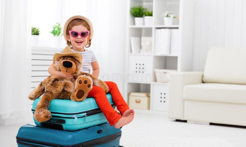 La muchacha feliz del niño recoge la maleta el vacaciones foto de archivo