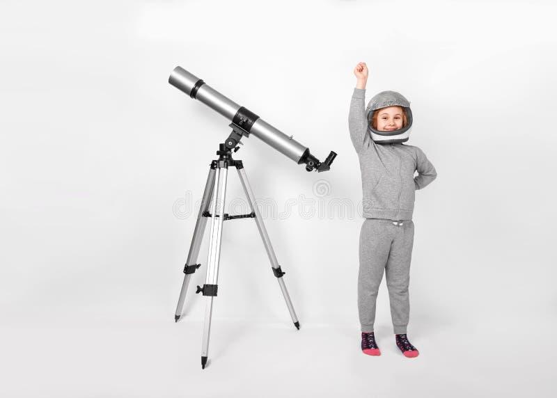 La muchacha feliz del niño se vistió en un traje del astronauta que se colocaba al lado del telescopio foto de archivo libre de regalías