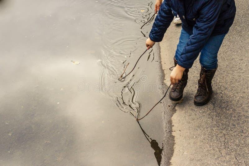 La muchacha feliz del niño y las botas de cuero marrones en charco en un otoño caminan La niña pequeña después de la lluvia corre imagen de archivo