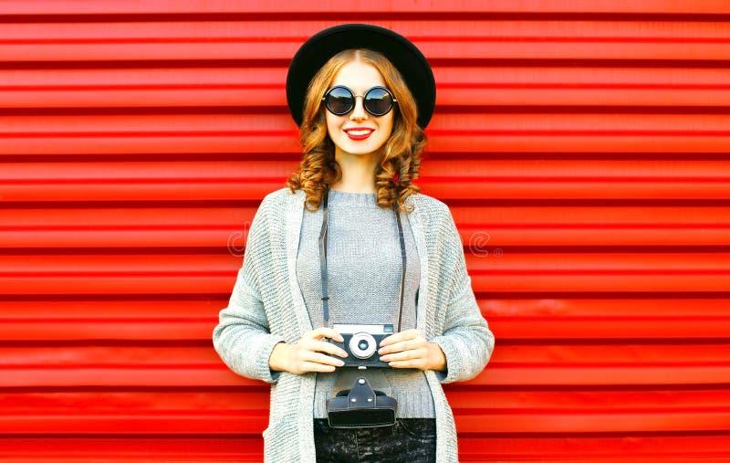 La muchacha feliz del otoño bonito sostiene la cámara retra en fondo rojo fotos de archivo