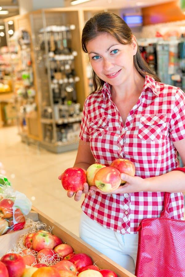 La muchacha feliz elige las manzanas en supermercado fotos de archivo libres de regalías