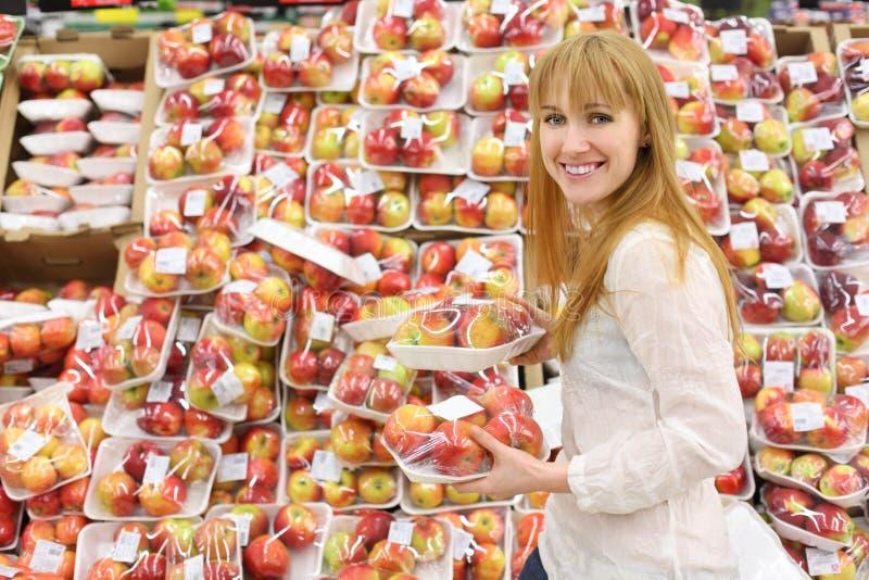 La muchacha feliz elige manzanas pila de discos en almacén fotografía de archivo