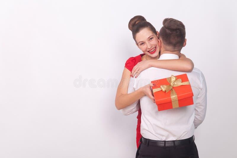 La muchacha feliz ha recibido un regalo, sonrisa dentuda, abraza a su hombre fotografía de archivo libre de regalías